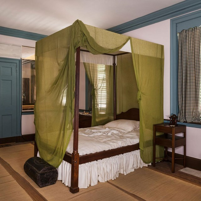Color photo of a bedroom with four poster bed draped with green cloth.