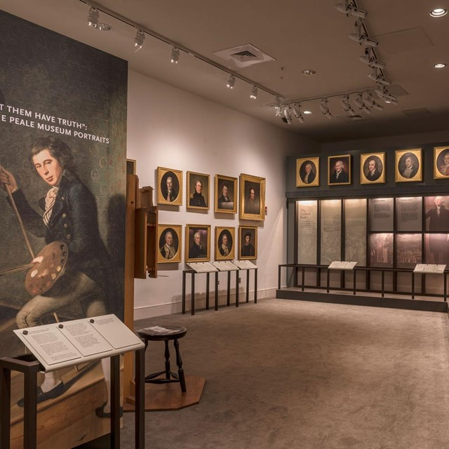 Color photo of exhibit area with a picture of one man (foreground) with rows of portraits behind.