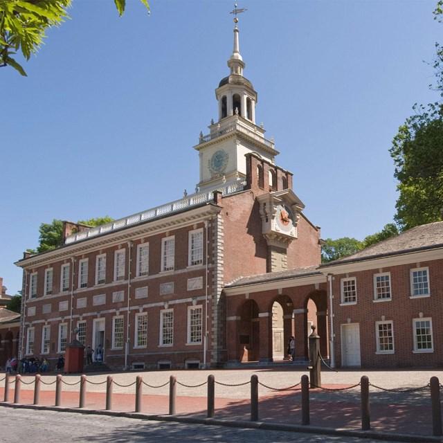 Color photo of Independence Hall, a two story red brick building with bell tower.