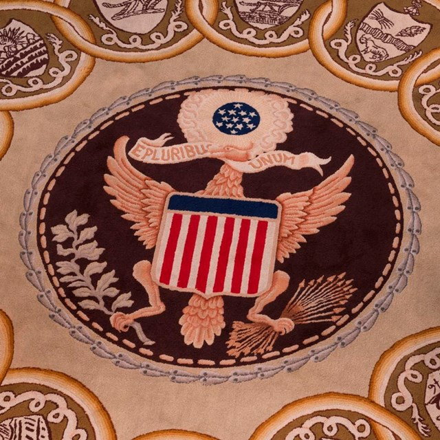 Color photo showing a detail from a carpet featuring the Great Seal of the U.S.