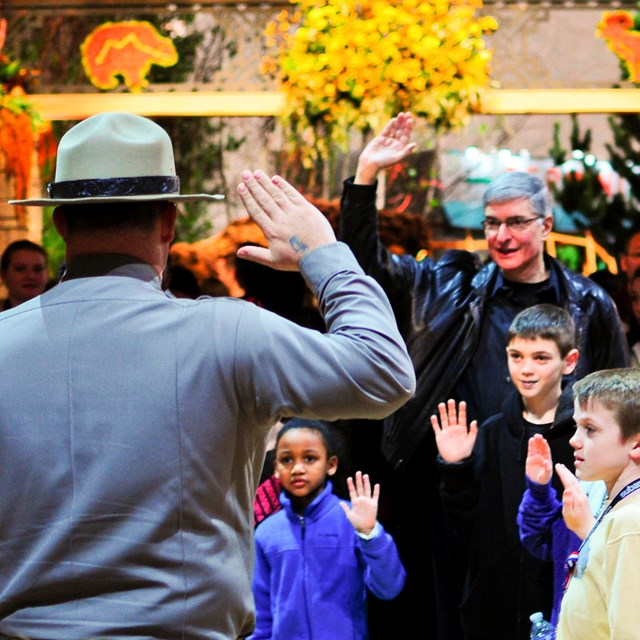 Color image of a park ranger holding up his hand as he swears kids in as junior rangers.