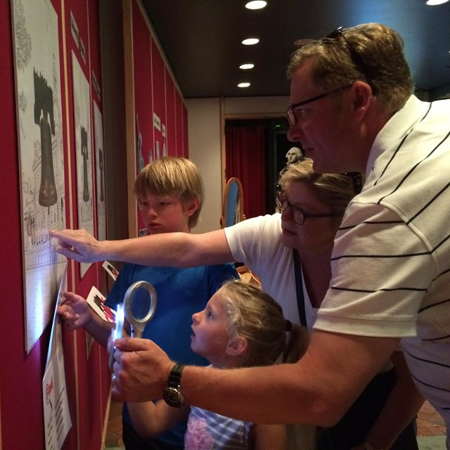 Color photo of a mom, dad, and two kids holding a magnifying glass, and looking at a picture.