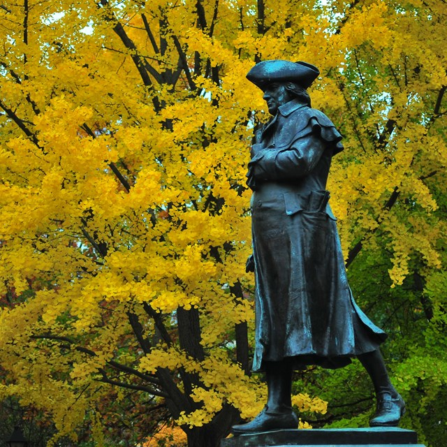 Color photo of a statue of a man in 18th century garb with fall foliage in the background.