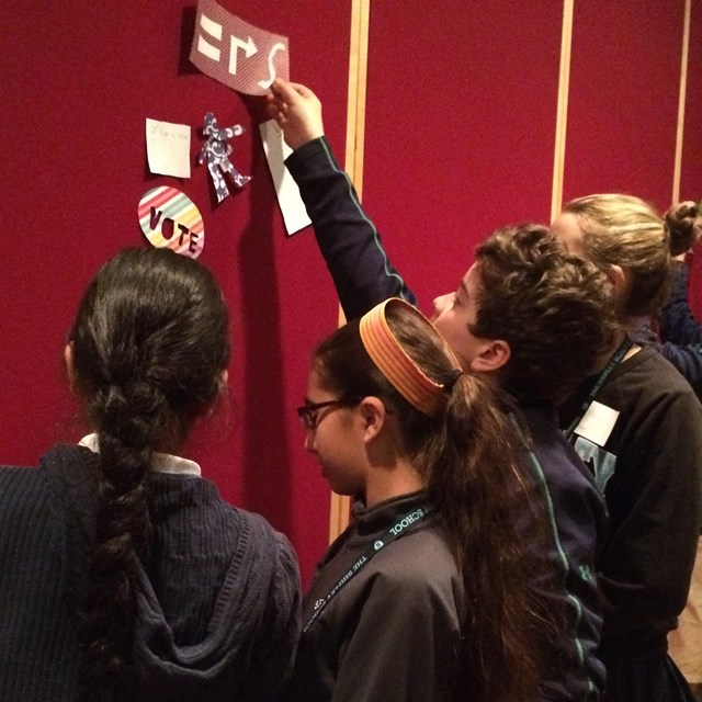 Color photo of a small group of teens places pictures on a velcro board.