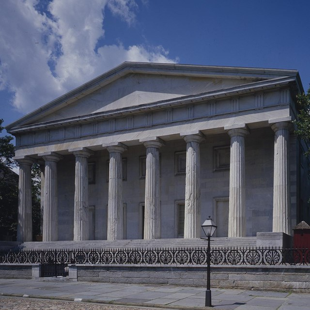 Color photo of a two-story marble building with several columns supporting a triangular pediment.