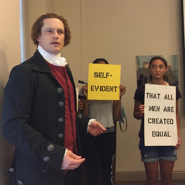 Color photo of a man in colonial costume in front of teens holding phrases from the Declaration.