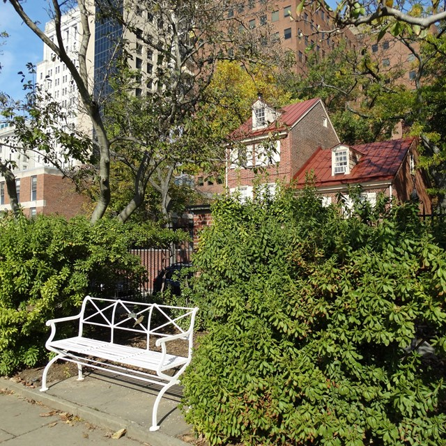 Color photo of white bench among foliage with a red brick house in the background.