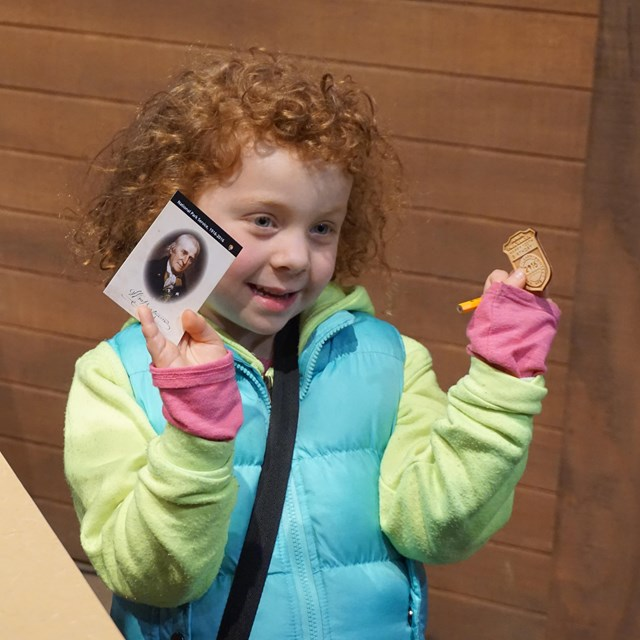 Color photo of a young girl holding up a Junior Ranger badge and a trading card.