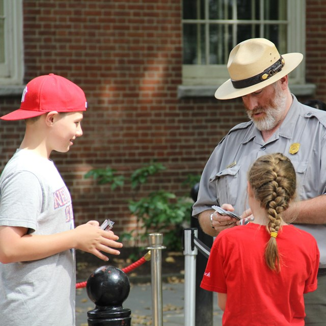 Color photo of a male park ranger standing outdoors, handing trading cards to a boy and girl.