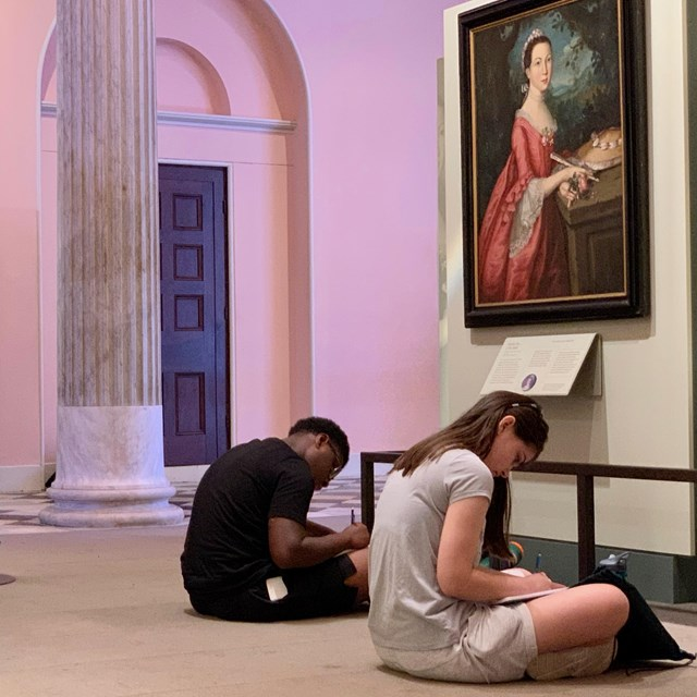 Color photo of three students seated on the floor below a portrait of a woman from the 1700s.