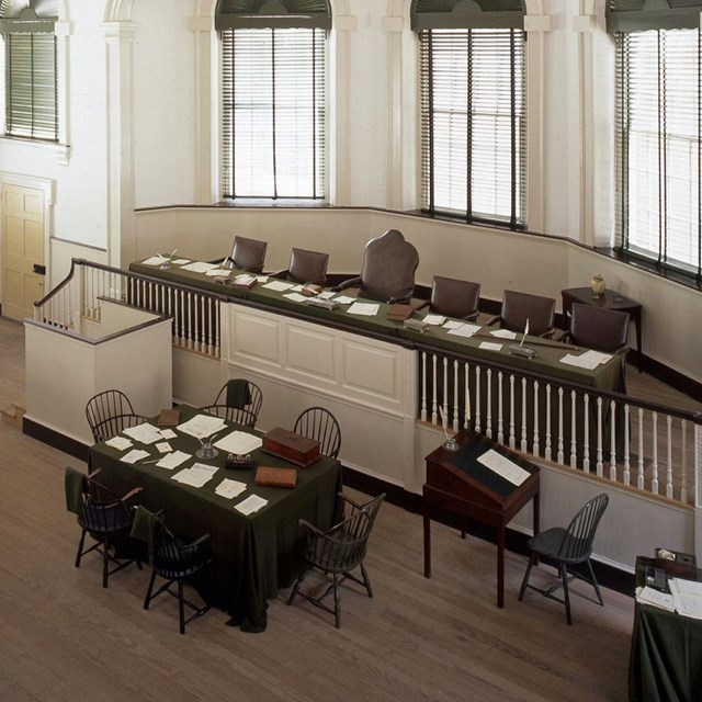 Color photo looking down on courtroom, showing raised bench for judges with table below.