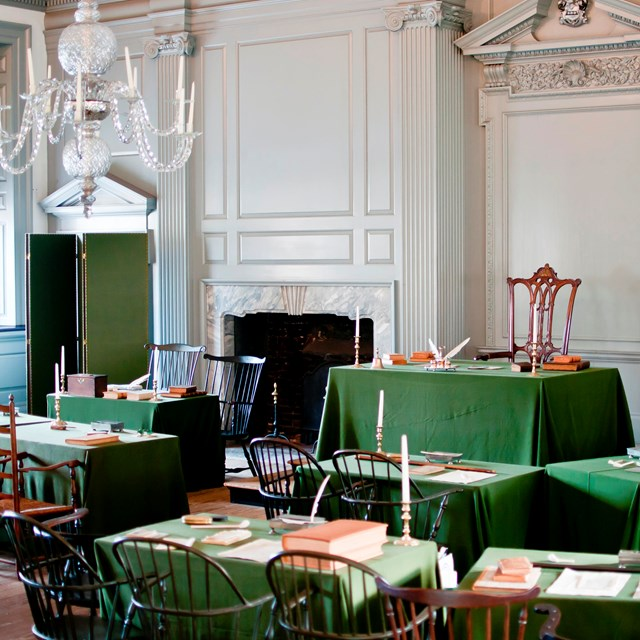 Color photo of Assembly Room with green cloth-covered tables facing a single table up front.