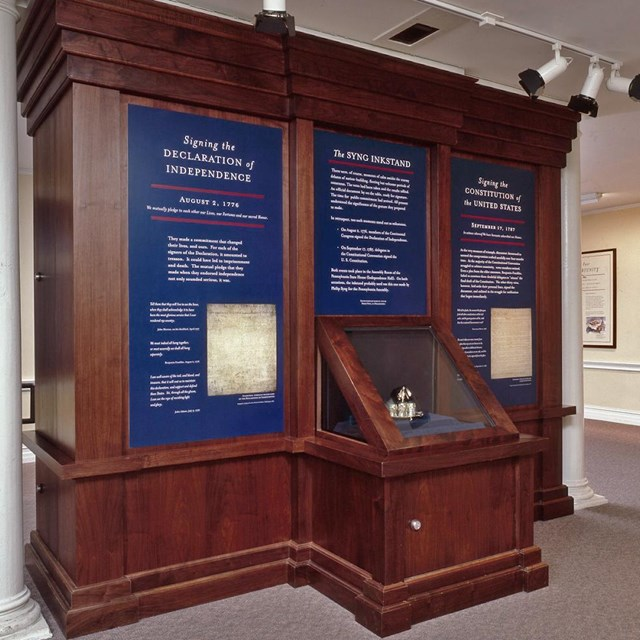 Color photo of exhibit case with text panels and silver inkstand.