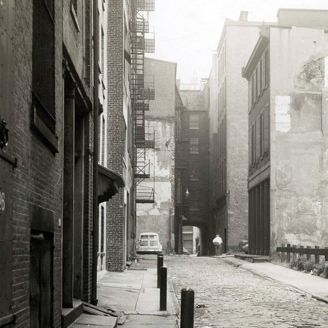 Black and white photo of a narrow alley lined with multi-story buildings.