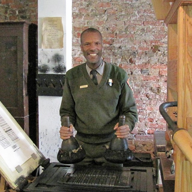 Color photo of male park ranger holding inking tools near a copy of an 18th century printing press.