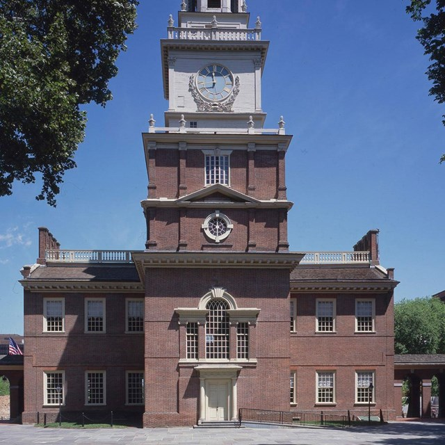Color photo of a large, two story red brick building with Palladian style window and clock tower.