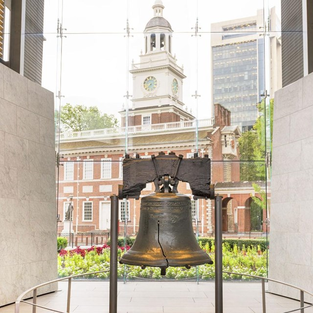Color photo of the Liberty Bell with a red brick building visible through the glass wall behind it.