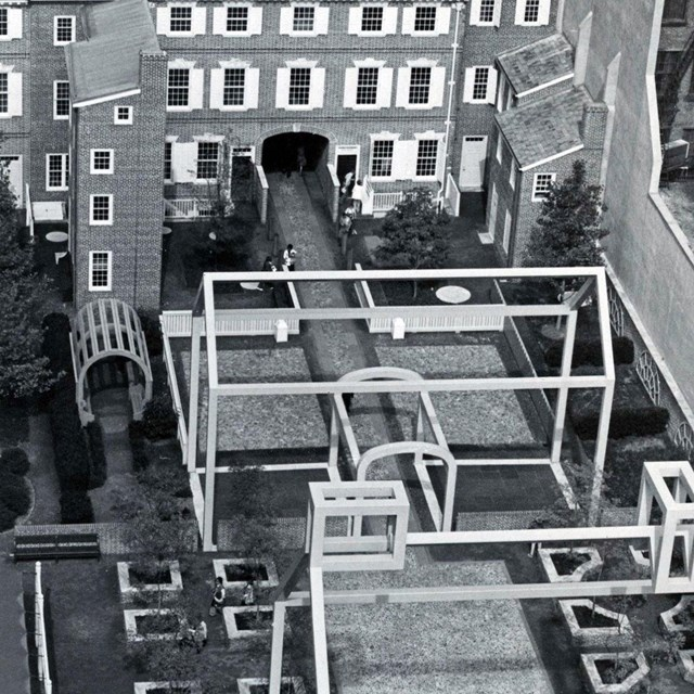 Black and white aerial view photo showing a courtyard with two steel frame house structures.