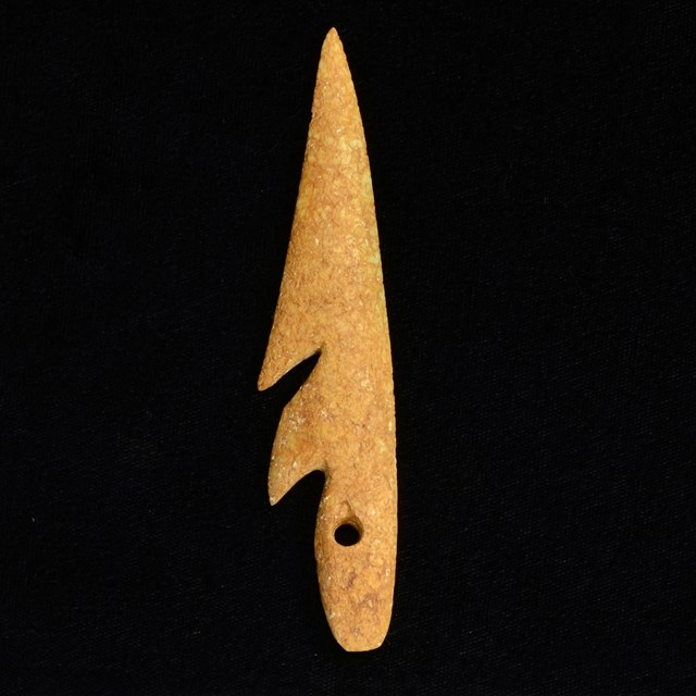 Carved fish hook on black background with ruler.