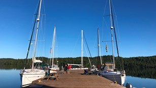 Multiple sailboats are docked around a large, wooden dock.
