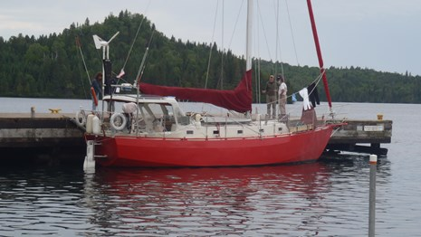 A red sailboat is tied to a dock with an island in the background and water.