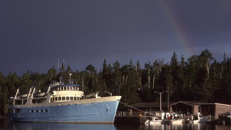 Ranger III ferry docked at the Rock Harbor Visitor Center with a rainbow in the sky.