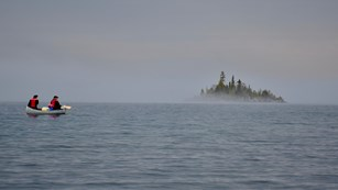 A silver canoe paddles toward an island surrounded by fog on a large body of water.
