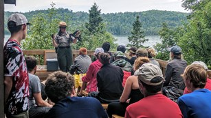 A female park ranger stands in front of a group of people seated on benches with a frog puppet on.