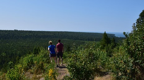 Two Hikers enjoy an overlook of the Isle Royale forest and the distant Lake Superior shoreline.