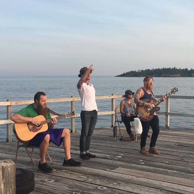 A photo shows four men playing music on a dock with water in the background