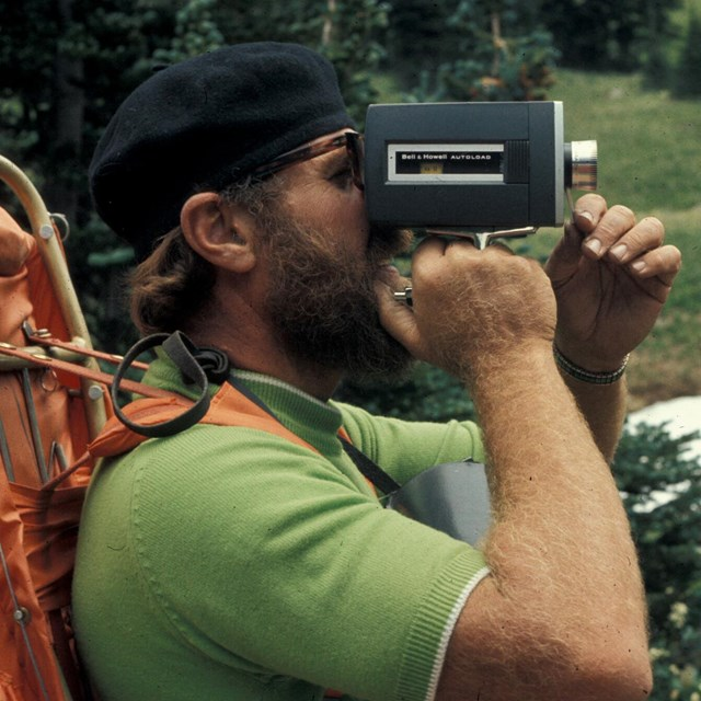 Image shows a man holding an old video camera with a large backpack on