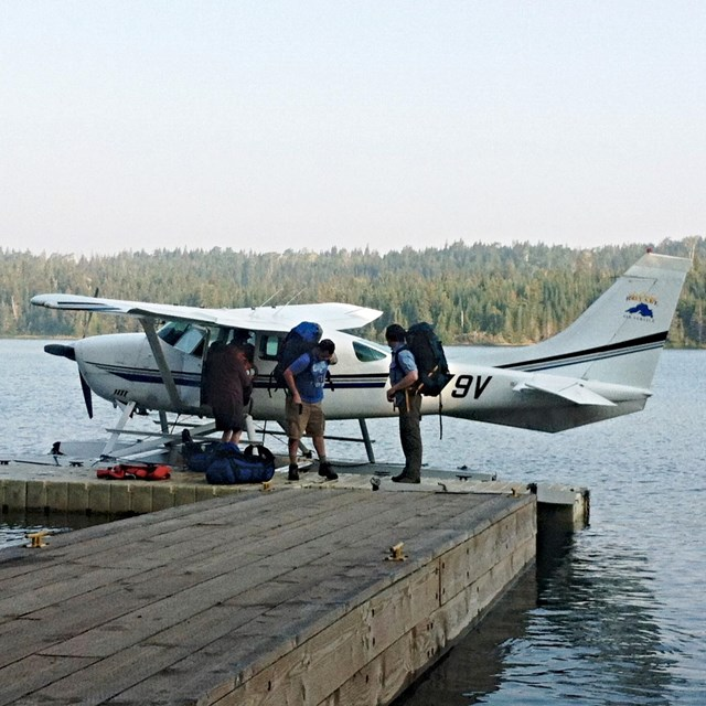 A white and red seaplane sits parked on a floating dock.