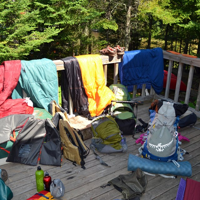 Backpacking gear spread out on a deck, life jacket, water bottles, clothing, tent supplies, etc.
