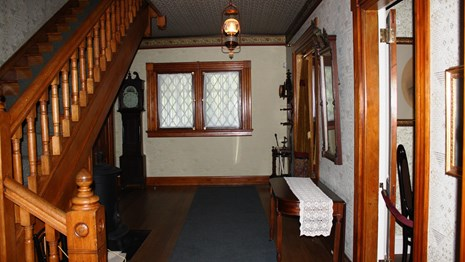 Entry hall with original 1880's woodwork and reproduction wallpaper.