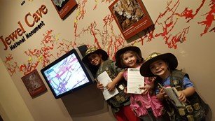 Three Junior Rangers stand in front of a large cave map, holding their activity booklets.