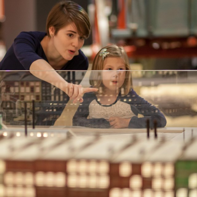 a woman and child examining a model of the St. Louis Levee