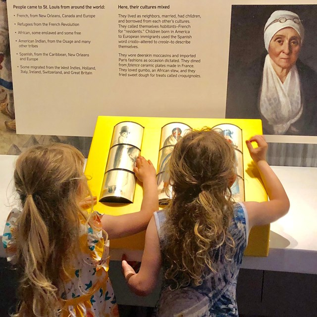 girls using interactive clothing spinner in Colonial gallery
