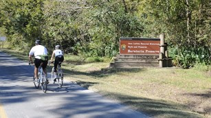 Bicyclists ride by the Barataria Preserve sign