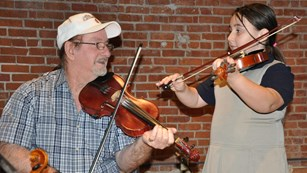 Man and little girl playing fiddles