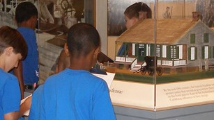 Boys looking at model of old house