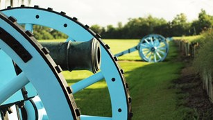 Cannons lined up behind wood and mud rampart