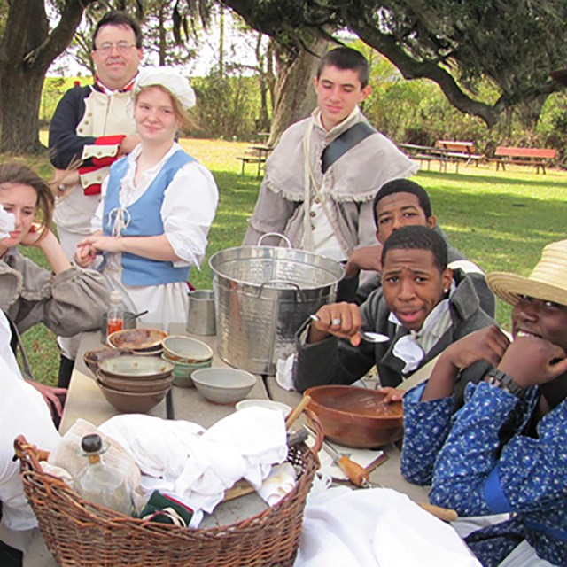 a group of reenactors dressed in period dress around a picnic table
