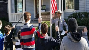 A uniformed Park Ranger performs a Junior Ranger swearing-in ceremony in front of the JFK Birthplace