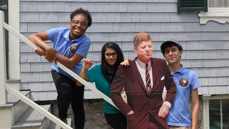 three teen stewards stand at the back steps of JFK National Historic Site.