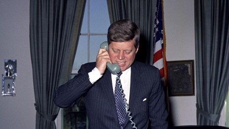 President Kennedy talks on the phone in the oval office, standing behind his desk.