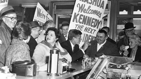 JFK seated at a lunch counter.  Supporters gather around him.