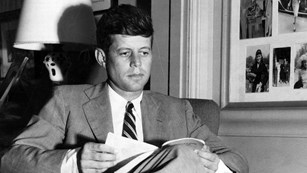 A Young JFK sits in an armchair reading a book.  Framed photos are seen on the wall next to him