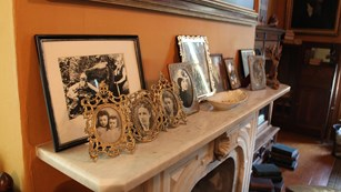 Fireplace mantel with multiple picture frames including photos of family.