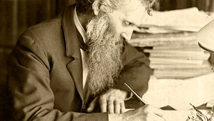 An older John Muir is writing at his desk.