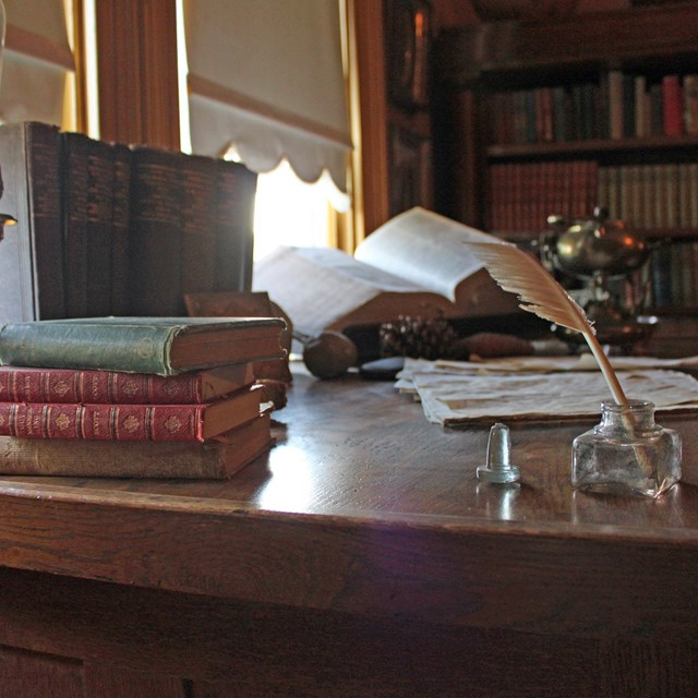 A quill and books sit on the corner of John Muir's desk.